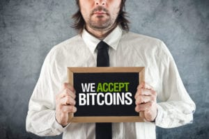 Businessman holding board with title WE ACCEPT BITCOINS as form of payment.